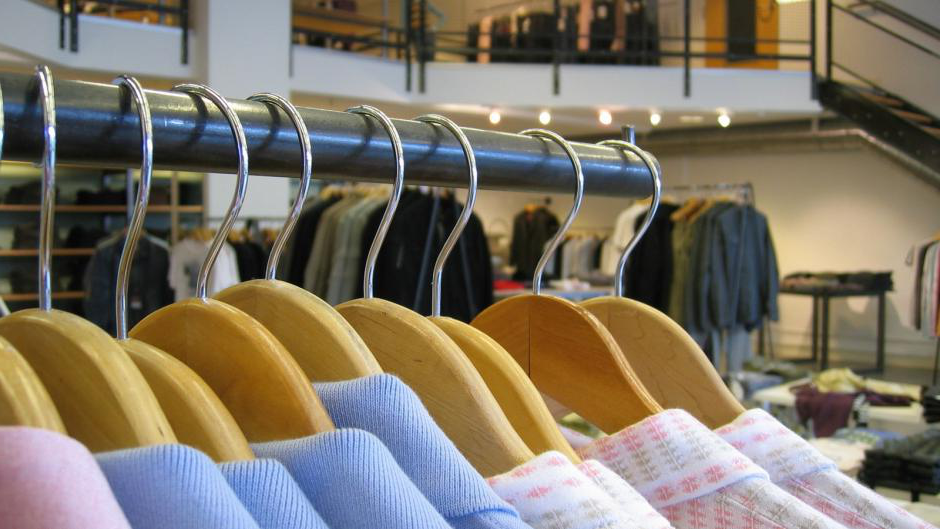 A male clothing store with casual and business attire on the racks